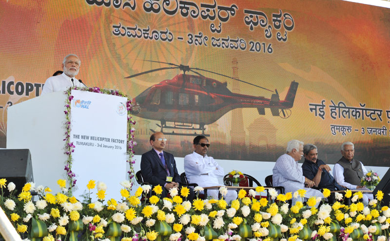 The Prime Minister, Mr. Narendra Modi addressing at the foundation stone laying ceremony for HAL Helicopter Factory, at Tumakuru, Karnataka on January 03, 2016. The Governor of Karnataka, Mr. Vajubhai Rudabhai Vala, the Union Minister for Defence, Mr. Manohar Parrikar and other dignitaries are also seen.