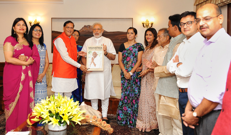 The Prime Minister, Mr. Narendra Modi receiving a book 'Mahatma Gandhi's Life in Colour', compiled and published by Gandhi Serve India from Bindeshwar Pathak, in New Delhi on October 02, 2016.