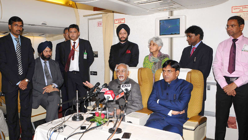 The Vice President, Mr. M. Hamid Ansari addressing the media on board, Air India One Special Aircraft on his way back to New Delhi after five-day visit to Hungary and Algeria, on October 19, 2016. The Minister of State for Road Transport & Highways, Shipping and Chemicals & Fertilizers, Mr. Mansukh L. Mandaviya is also seen.